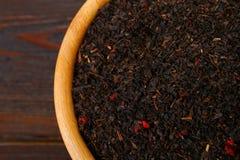 黑干茶用在一个碗的一棵樱桃在一张木桌上 免版税库存照片