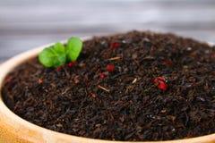 黑干茶用在一个碗的一棵樱桃在一张木桌上 免版税库存图片