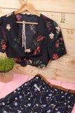黑庄稼上面/女衬衫在花卉图案在挂衣架、蓝色裙子、传送带和首饰垂悬:头发珍珠夹子,项链,耳环 库存照片