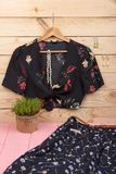 黑庄稼上面/女衬衫在花卉图案在挂衣架、蓝色裙子、传送带和首饰垂悬:头发珍珠夹子,项链,耳环 库存图片