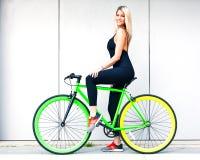 黑性感的成套装备的美丽的白肤金发的女孩在灰色墙壁附近在一个夏日坐一辆固定的绿色自行车 免版税图库摄影