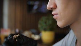 黑手套的吃在咖啡馆,慢动作的人饥饿的年轻人一个汉堡 股票视频