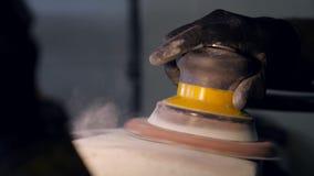黑手套的工作者与在车身服务,慢动作的空气沙磨机一起使用 影视素材
