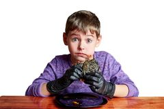 黑手套的男孩情感地吃汉堡的 免版税库存照片
