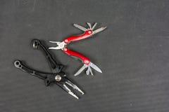 黑折叠为钓鱼者的钳子和红色多功能工具 库存照片