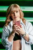 黑拿着在她的胳膊的胸罩和白色衬衣的美丽的年轻白肤金发的妇女智能手机 免版税库存照片