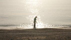 黑挖掘者的剪影有金属探测器的在岸的查寻在闪烁的太阳光芒背景在水的 股票录像