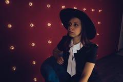 黑摆在红色背景的礼服和黑帽会议的女孩 图库摄影