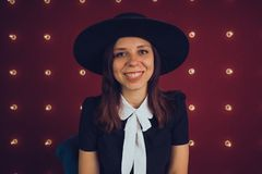 黑摆在红色背景的礼服和黑帽会议的女孩 库存照片