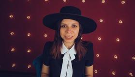 黑摆在红色背景的礼服和黑帽会议的女孩 免版税库存照片