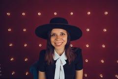 黑摆在红色背景的礼服和黑帽会议的女孩 免版税库存图片