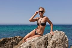 黑斜倚在岩石的比基尼泳装和被设色的太阳镜的妇女 免版税库存图片