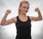 黑无袖衫的年轻女人与哑铃 免版税图库摄影