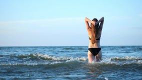 黑时兴的泳装的性感的女孩进入海 女孩浸入入水,徒步走 晚上在 股票视频