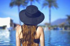 黑时尚帽子、红色嘴唇和长的头发的年轻美丽的微笑女孩,摆在棕榈附近水池beackground  免版税库存照片
