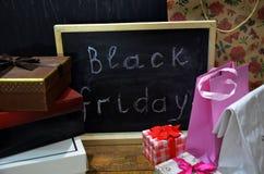 黑星期五手写与在一个黑板的白色白垩在木背景 包裹,箱子,购物 库存照片