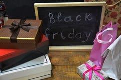 黑星期五手写与在一个黑板的白色白垩在木背景 包裹,箱子,购物 免版税库存照片