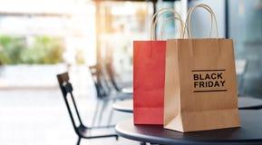 黑星期五销售和购物袋在购物中心桌前面  免版税库存照片