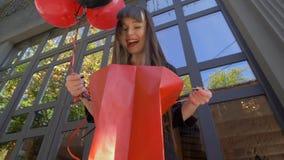 黑星期五,愉快的shopaholic女孩惊奇地在纸袋看和愉快地微笑与气球 股票录像
