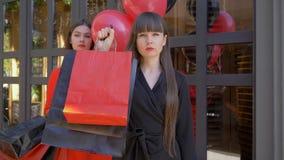 黑星期五,显示全部有购买的纸袋的严肃的女孩画象在有气球的女朋友前在黑暗 股票视频