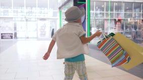 黑星期五,有购物袋的快乐的孩子在手中对在购物中心的新的购买满意 影视素材