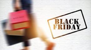 黑星期五,被弄脏的妇女运载的购物袋 库存照片