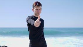 黑显示的赞许的年轻适合的可爱的帅哥对在海滩的照相机身分 强的波浪击中bea 股票录像