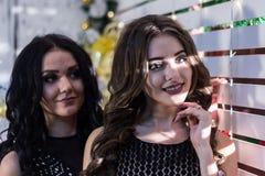 黑晚礼服的两个美丽的女孩在明亮的光在面孔落的一个白色格子附近 新年或Chri 图库摄影