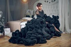 黑晚礼服的美丽的妇女坐在豪华内部的床 方式射击 女孩去党 免版税图库摄影