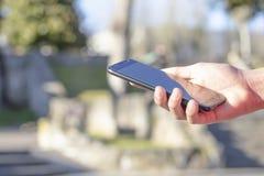黑智能手机在手中在露天公园,点燃由太阳 免版税库存照片