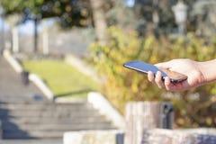 黑智能手机在手中在露天公园,点燃由太阳 图库摄影