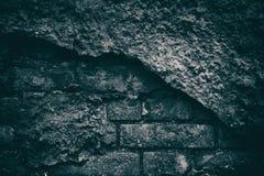 黑暗令人毛骨悚然的背景风化了有残破的plaste的砖墙 库存图片