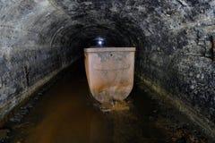 黑暗充斥了具体有圆顶排水设备矿隧道 图库摄影
