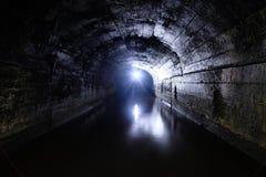 黑暗充斥了具体有圆顶排水设备矿隧道 免版税图库摄影