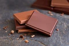 黑暗和牛奶巧克力四个正方形与小巧克力位在灰色板岩 被弄脏的巧克力在背景中 库存图片