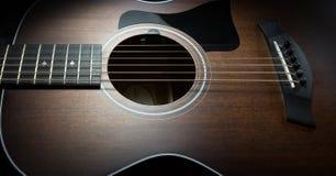 黑暗树木繁茂的声学吉他 免版税库存照片