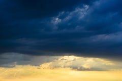 黑暗的云彩忽略美好和温暖的日落 图库摄影