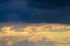 黑暗的云彩忽略美好和温暖的日落 免版税库存照片