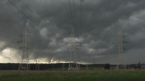 黑暗的云彩横跨天空漂浮反对电力定向塔 股票录像