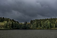 黑暗的具球果森林一个大池塘有黑暗,恐怖的云彩的 免版税图库摄影
