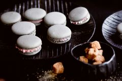 黑暗的单色摄影 灰色在桌的黑暗的表面结块蛋白杏仁饼干,在一个匙子和糖罐旁边与 免版税图库摄影