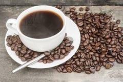 黑暗的咖啡豆包围的通入蒸汽的热咖啡与 库存照片