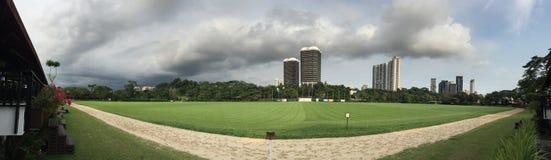 黑暗的在马球俱乐部新加坡的天空草坪全景 免版税库存照片