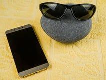 黑暗的太阳镜在一个大海小卵石和智能手机穿戴了 图库摄影
