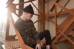 黑暗的太阳镜的好时髦的年轻行家人在一件时髦绿色军用衬衣的一个时兴的帽子在牛仔裤放松坐 图库摄影