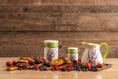 黑暗的巧克力饼干用新鲜的森林果子和陶瓷船在木桌上 免版税库存图片