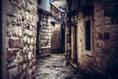 黑暗的有古老石大厦门面的葡萄酒中世纪狭窄的绕街道与中世纪建筑学在老欧洲城市Kot 库存照片