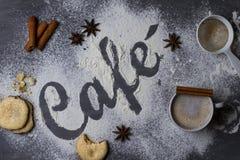黑暗的桌装饰用由小麦面粉做的词咖啡从顶向下被拍摄,加上一个大杯子新鲜的咖啡 免版税图库摄影