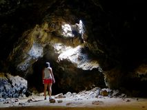 黑暗的洞的妇女从熔岩管 库存图片