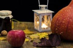 黑暗的秋天静物画用南瓜、蜡烛和灯,有yello的 免版税库存照片
